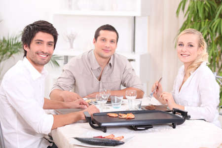 Friends cooking dinner on a tabletop hot plate Stock Photo - 13951365