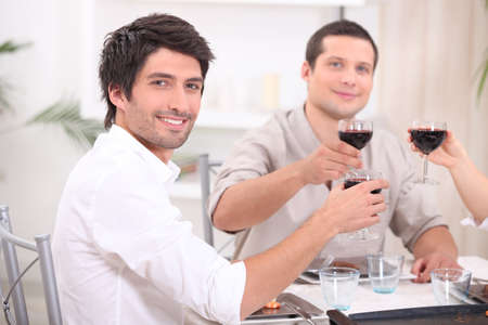 rolled up sleeves: young people clinking glasses with red wine Stock Photo