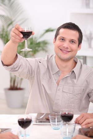 convivial: Man raising his glass for a toast