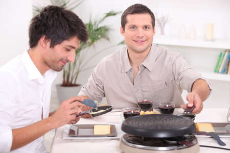Two men enjoying a Raclette Stock Photo - 13950388