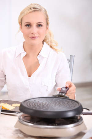 blonde woman in front of a heater preparing melted cheese, potatoes and cold meat (raclette) photo