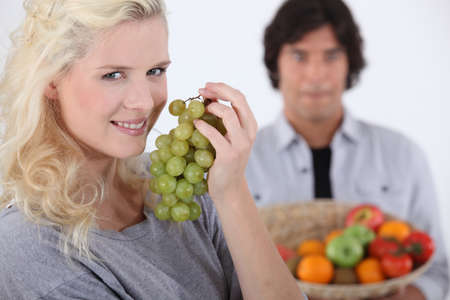 pretty smiling blonde eating grapes photo