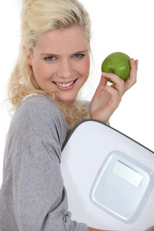 woman on scale: Woman with an apple and a scale