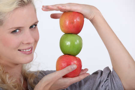 chirpy: young blonde holding pile of apples Stock Photo