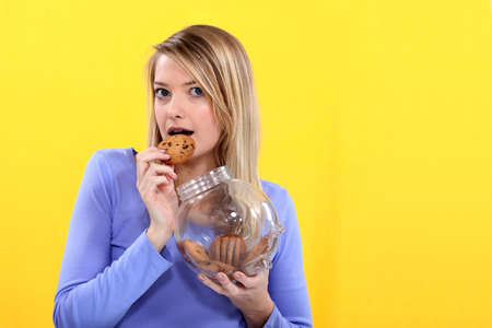 to tempt: Woman eating biscuit from jar Stock Photo