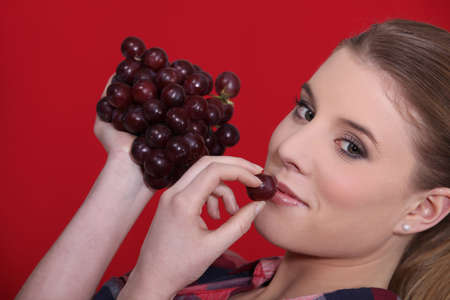 Woman eating grapes Stock Photo - 13960297