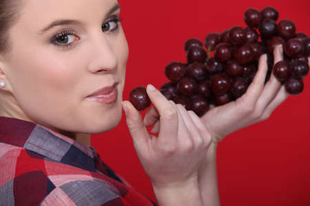 Woman eating grapes photo