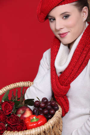 Woman in a red scarf and hat with red food and roses photo