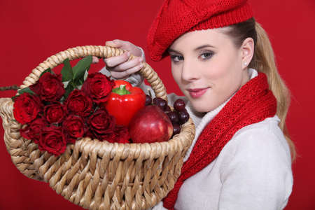 lovely blonde carrying basket filled with red and dressed to match Stock fotó