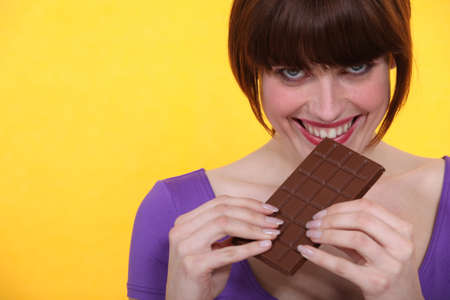 relishing: young woman relishing chocolate bar against yellow background