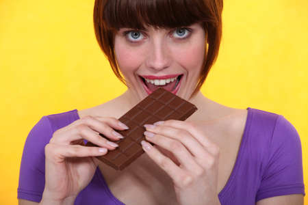 guilty pleasure: Gourmand woman eating chocolate Stock Photo