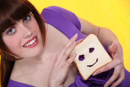 Woman with a smiley face carved into bread photo