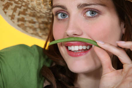 Woman pretending green bean is a mustache photo