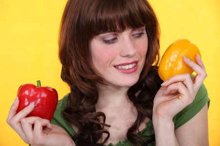 Woman holding red and yellow peppers photo