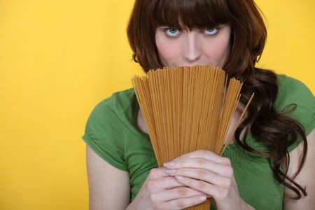 beautiful brunette holding spaghettis isolated on yellow photo