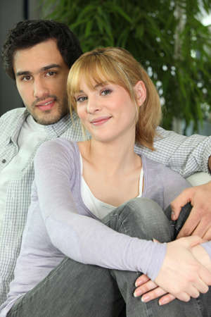 teen couple: Portrait of young couple sitting in sofa Stock Photo