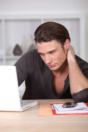 young handsome man working on laptop Stock Photo - 13951106