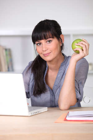 Woman with an apple sitting at her laptop photo
