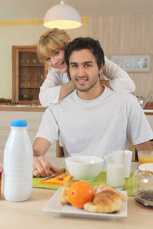 Smiling man and woman having breakfast photo