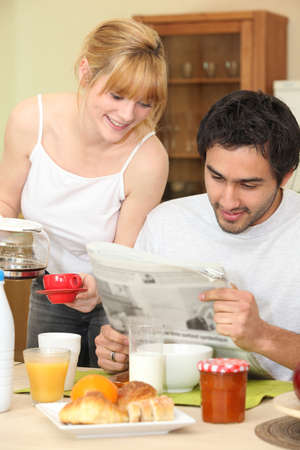 Couple having breakfast with newspaper photo