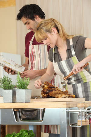Couple cooking roast chicken photo