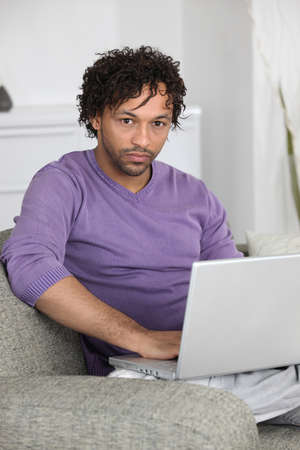 impersonal: unhappy man doing computer on a couch
