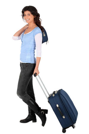 Woman pulling a small suitcase photo