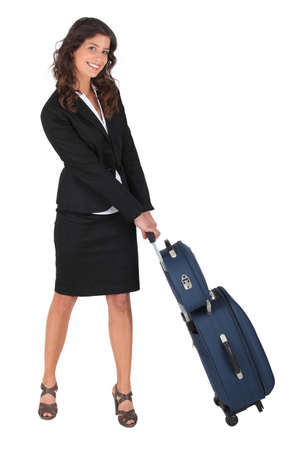 Woman pulling a carry-on case photo
