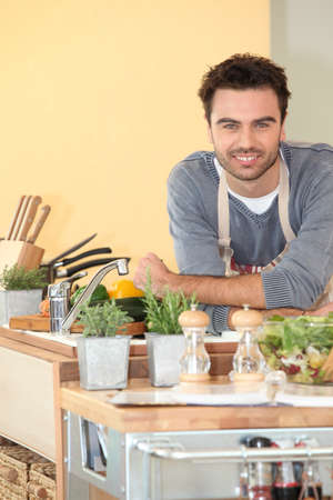 young handsome man: Smiling chap relaxed in his kitchen