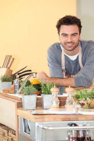 beau jeune homme: Sourire bonhomme détendu dans sa cuisine