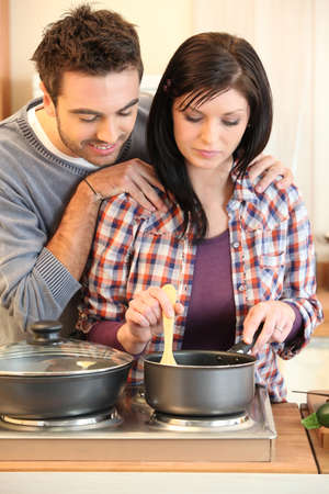 Young married couple cooking dinner photo
