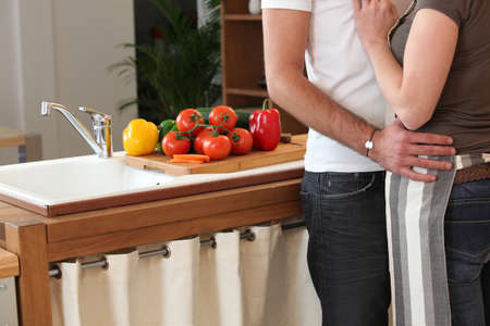 waist deep: couple hugging tenderly in the kitchen