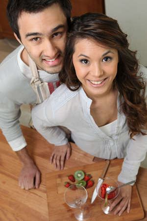 all smiles: high angle shot of couple all smiles slicing fruits Stock Photo