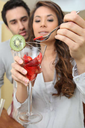 Couple eating strawberries from a glass photo