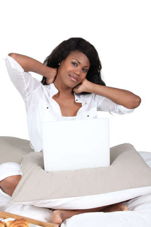 Woman rubbing her neck while using a laptop on her bed photo