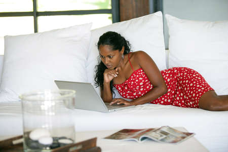 beautiful Afro-American woman lying on her bed with her laptop photo