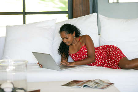 Sexy woman using her laptop on a couch photo