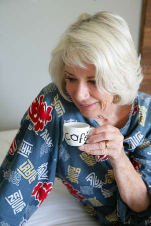 wise woman: Grey-haired lady drinking her morning coffee Stock Photo