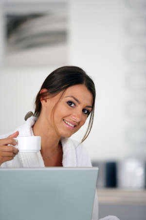 Woman having a cup of coffee in front of her laptop photo