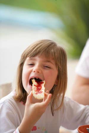 comiendo pan: Ni�a comiendo pan con mermelada en ella Foto de archivo