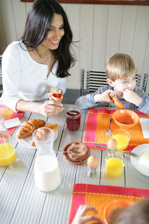 Mother and son eating breakfast at the table photo