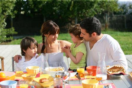 niños desayunando: Familia con desayuno-almuerzo fuera en un día soleado Foto de archivo