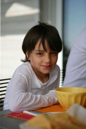 niños desayunando: Chico joven en la mesa de desayuno Foto de archivo