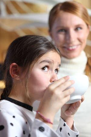 Little girl drinking from breakfast bowl photo