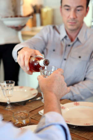 Man pouring wine during meal photo