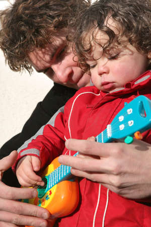 Boy and father plying with toy guitar photo