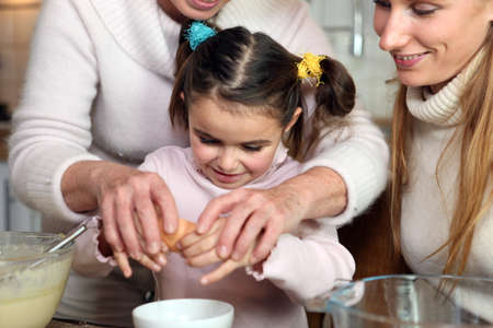 cracking: Little girl baking with her family Stock Photo