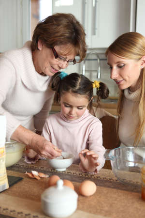 Little girl preparing cake with her mother and her grandmother photo