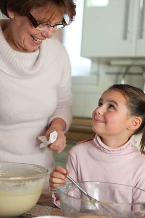 Little girl cooking with grandma photo