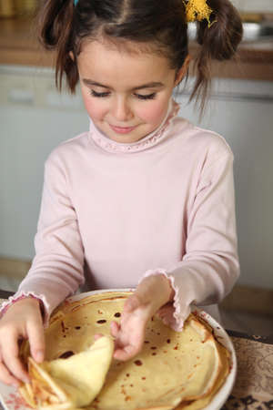 Little girl preparing pancakes Stock Photo - 13949684